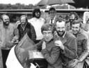 De NOS-equipe voor de Tour de France van 1978. Op de motor van links naar rechts Theo Koomen, Hans Prakke en Heinze Bakker, daarachter van links naar rechts de discjockeys Joost den Draaier, Ferry Maat, Felix Meurders, Jan van Veen en Lex Harding.