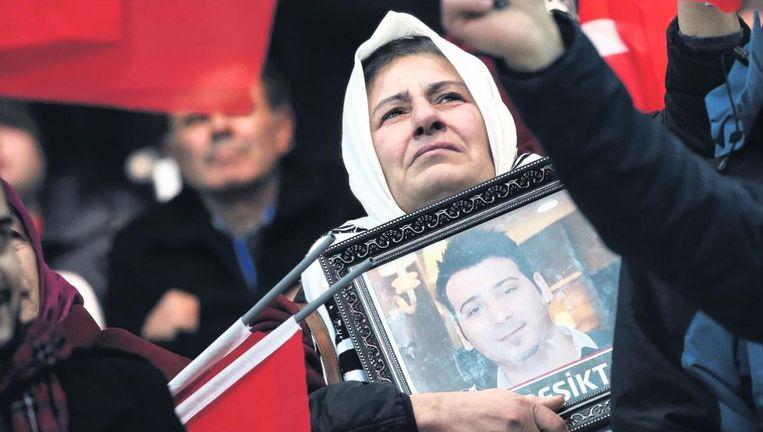 Een moeder houdt de foto van haar gestorven zoon vast tijdens de voetbalwedstrijd die speciaal voor de familie van omgekomen martelaren werd georganiseerd Beeld ap