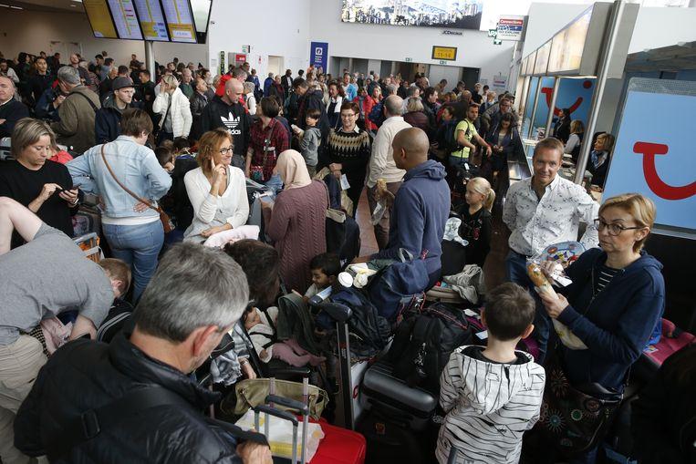 Passagiers moeten wachten op Brussels Airport door de staking van Aviapartner. Beeld BELGA