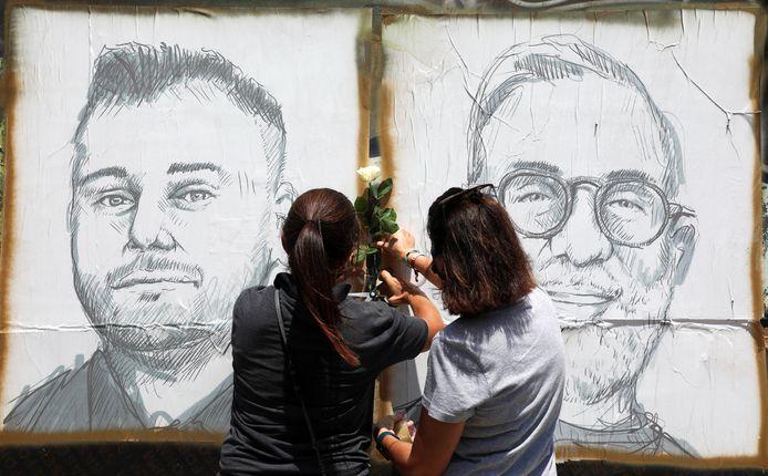 Mensen plaatsen bloemen bij afbeeldingen van slachtoffers van de dodelijke explosie in de haven van Beirut vorig jaar.