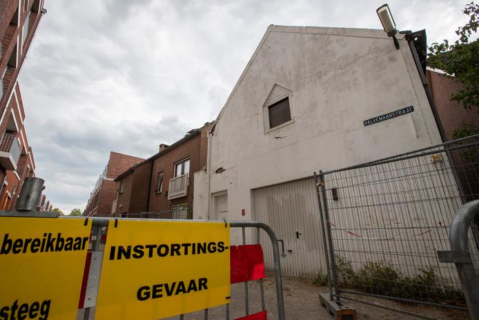 De kop van de Halvemaanstraat, met rechts de vervallen loods en links het appartementencomplex. De loods staat op instorten en wordt al jarenlang amper gebruikt.