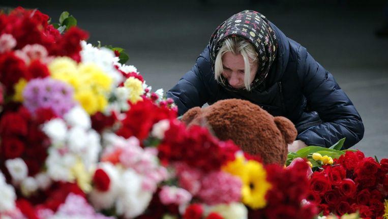 Mensen leggen bloemen neer in bij een vliegveld in Sint Petersburg Beeld ANP