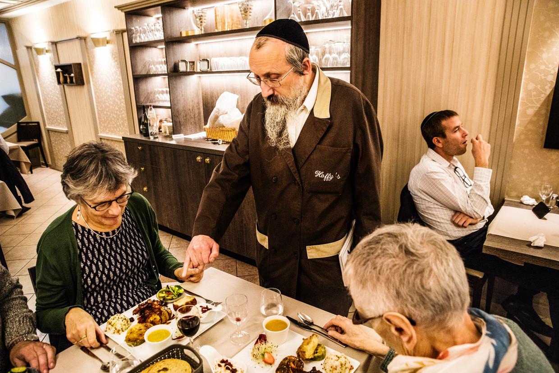 Benjamin Hoffman geeft uitleg aan Belgische gasten over de tradities van de joodse keuken.  Beeld Aurélie Geurts