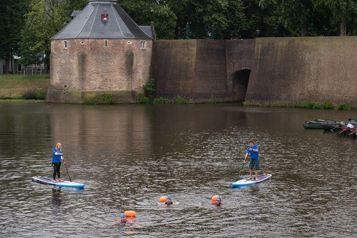 Breda - Pix4Profs/René Schotanus. Burgemeester Paul Depla (R), wethouder Daan Quaars (M) en oncoloog Hans Westgeest springen in het water en zwemmen een stuk voor Swim to Fight Cancer.