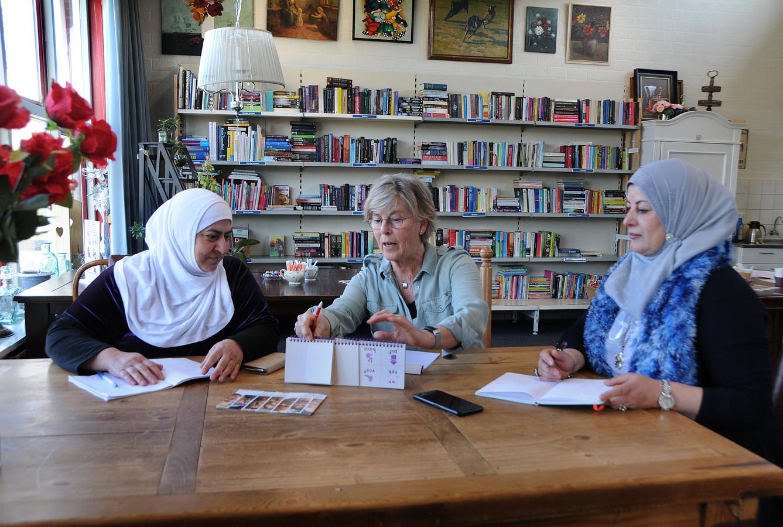 Ineke van Poppel-Louws geeft taalles aan Hekmat (r) en Buchra (l), twee uit Syrië afkomstige vrijwillige medewerksters bij de Ruilwinkel in Zierikzee.