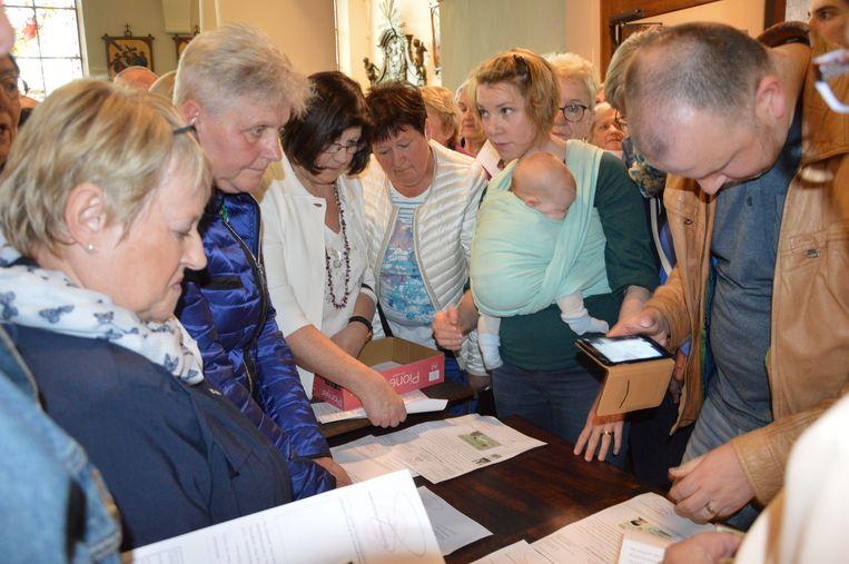 Wereldrecord Rita's verzamelen in kerk van Outer. De Rita's tonen hun identiteitskaart aan de gerechtsdeurwaarder.