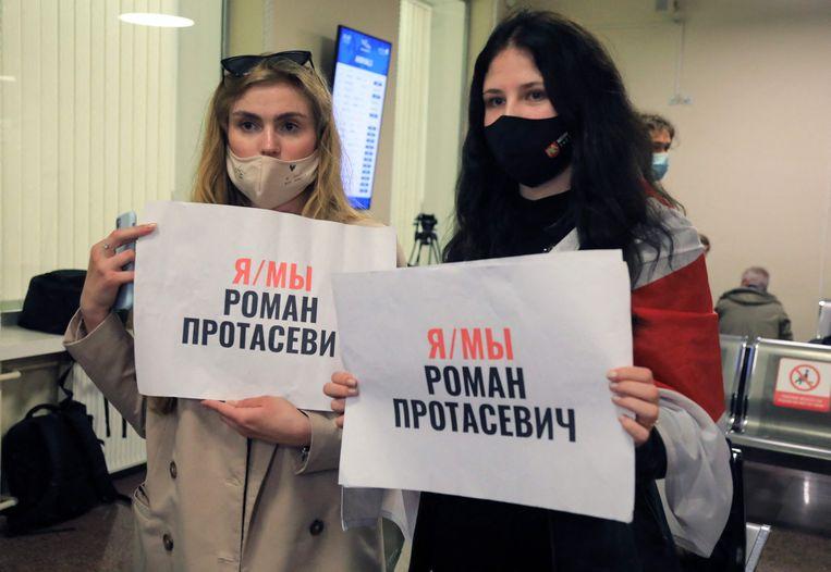 Medestanders van Roman Protasevitsj wachtten zondag tevergeefs op het vliegveld van de Litouwse hoofdstad Vilnius op zijn komst. Op hun posters staat: 'Ik ben/ Wij zijn Roman Protasevitsj'. Beeld AFP