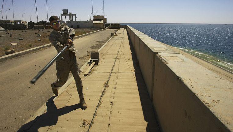 Een Amerikaanse soldaat slaat met een tentstok een steentje de Eufraat in vanaf de Hadhita-dam in 2005. Beeld ap