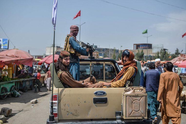 Taliban-strijders verplaatsen zich door een marktgebied in Kaboel.  Beeld AFP