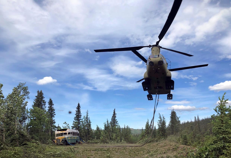 Een helikopter takelt het busje weg. Beeld via REUTERS