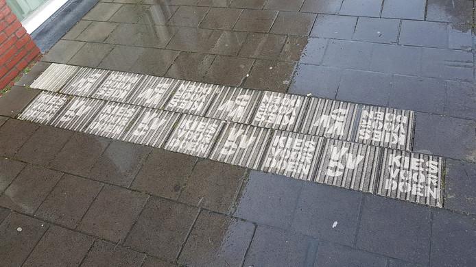 Met de hoge drukspuit heeft de VVD verkiezingsleuzen 'uitgespaard' op de vieze tegels.