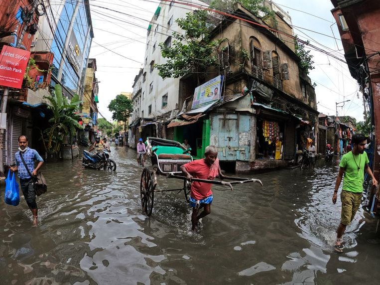 Een riksjarijder trekt eind juli in Kolkata, India zijn kar door straten die overstroomd zijn als gevolg van de hevige moessonregens. Beeld Getty