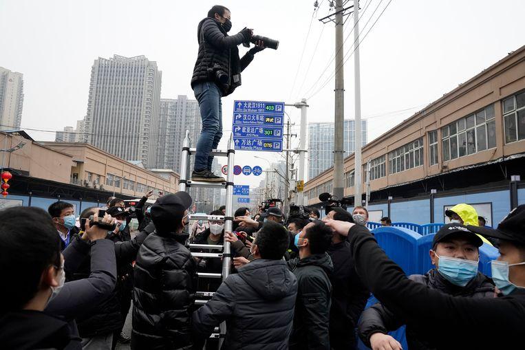 Fotografen en journalisten proberen een glimp op te vangen van Marion Koopmans en de andere leden van de WHO-missie bij hun bezoek aan de Huanan Seafood Market in Wuhan, die in verband wordt gebracht met de uitbraak van het coronavirus.  Beeld AP