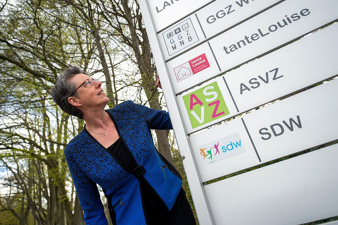 Ineke Strijp bij het bord bij de entree van het terrein van Landgoed Vrederust waar behalve GGZ WNB ook andere zorginstellingen neerstreken, een idee uit haar koker.