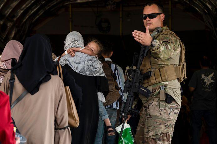 Een Amerikaanse soldaat leidt vrouwen en kinderen een evacuatievliegtuig in op de luchthaven van Kaboel.