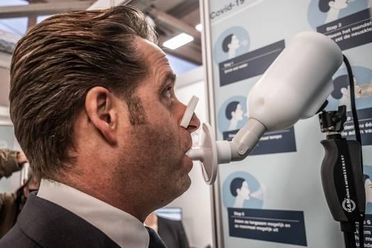 De SpiroNose is een ademtest die een coronabesmetting kan 'ruiken'. Hier doet demissionair minister Hugo de Jonge zo'n test.