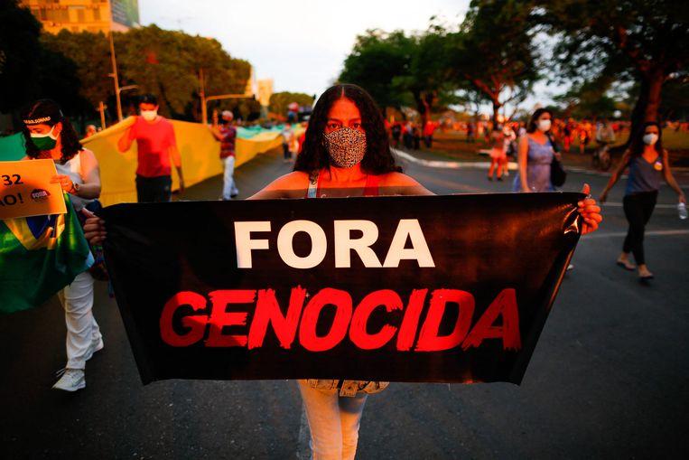 Een demonstrant tijdens de anti-Bolsonarobetoging in de hoofdstad Brasília. 'Weg met de genocide', luidt de tekst op het spandoek. Beeld AFP