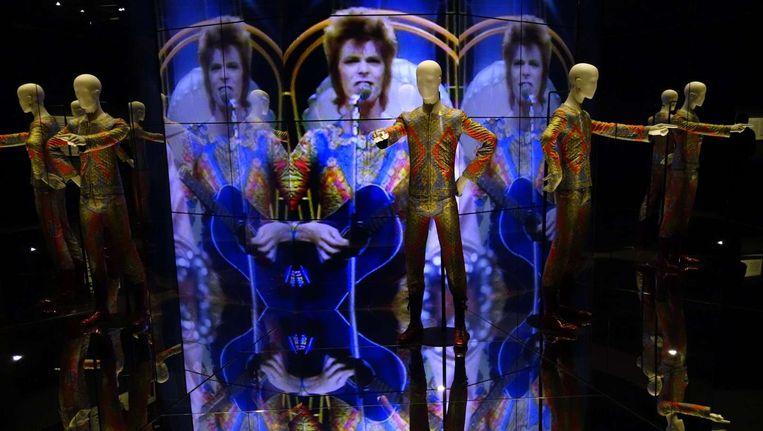 Het jumpsuit van Ziggy Stardust, met afbeeldingen van het personage in de achtergrond.