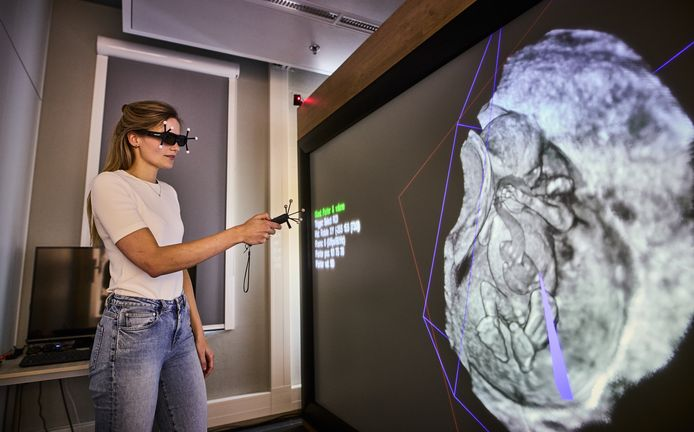 Arts-onderzoeker Naomi Graafland van het Erasmus MC in actie bij het grote scherm, waarop een hologram van een foetus rondzweeft.