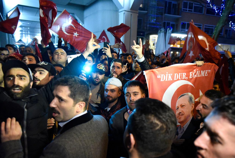 Demonstranten bij het Turkse consulaat in Rotterdam. Enkele aanwezigen maken het gebaar van de Grijze Wolven. Beeld Hollandse Hoogte / Peter Hilz