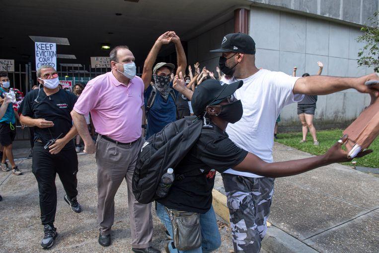 De demonstranten die opkomen voor de rechten van huurders proberen met de blokkade te voorkomen dat de door huisbazen ingeschakelde advocaten hun huisuitzettingszaak voor de rechter kunnen bepleiten. Op de foto pakt een demonstrant een dossier af, maar dat werd later teruggegeven. Beeld AP