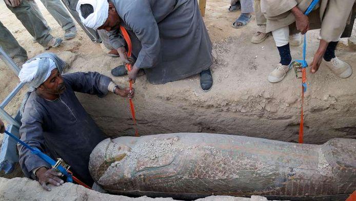 Een houten sarcofaag de in Egypte uit de grond wordt gehaald.