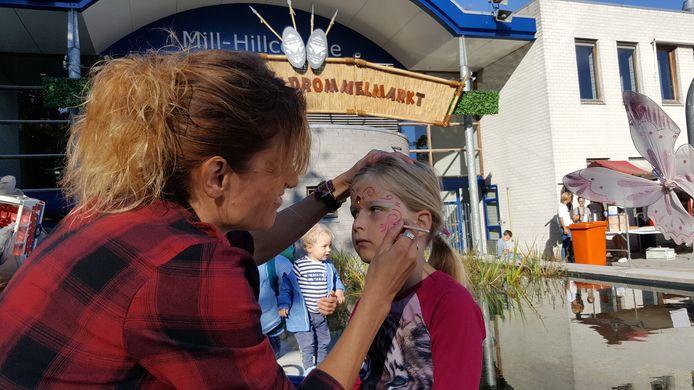 Daantje (5 jaar) wordt op het plein voor de school geschminkt.