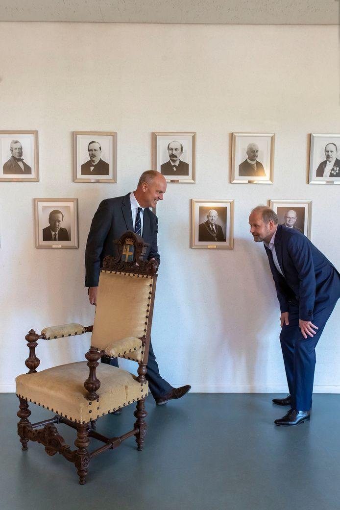 Burgemeester Patrick Welman bekijkt de stoel van een van zijn verre voorgangers, Gijsbert Waller, aandachtig. Frans Stork (links) die zich de antieke stoel vooral herinnert als 'sinterklaasstoel' geeft het antieke meubelstuk in bruikleen.