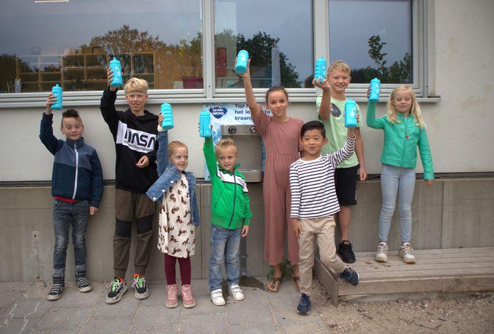 Ferre, Milan, Yinthe, Robin, Nubia, Bo, Tygo en Danique (vlnr)  zijn blij met het watertappunt.