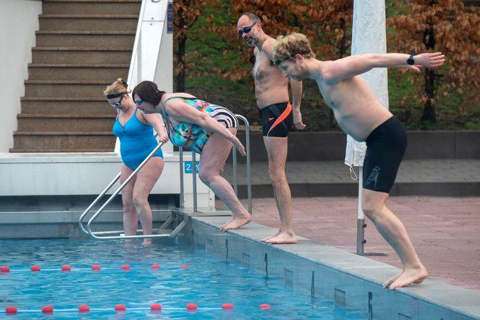 Het tweede uur van het banenzwemmen in zwembad Klarenbeek is zojuist van start gegaan. De een kiest voor het trapje om te water te gaan, de ander voor een stoere duik vanaf de kant.