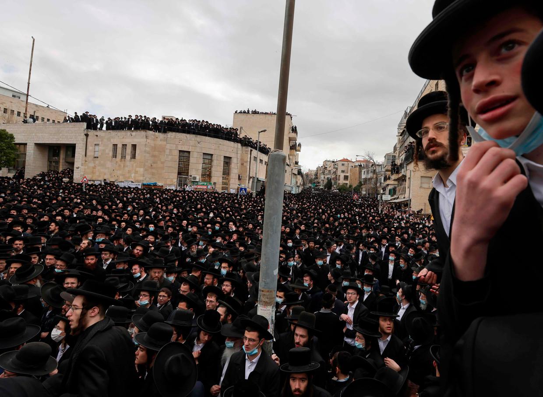 Duizenden ultra-orthodoxe joden wonen tijdens de lockdown een begrafenis van een belangrijke rabbi bij in Jeruzalem.  Beeld AFP