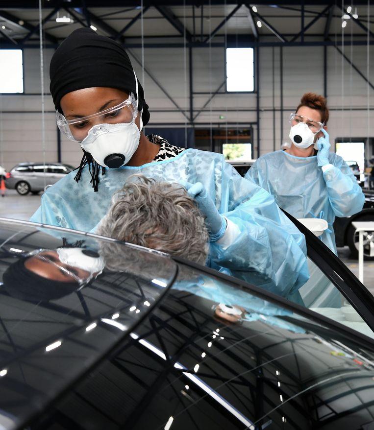 Een automobilist wordt getest op corona in de teststraat in Roosendaal. Beeld Marcel van den Bergh / de Volkskrant