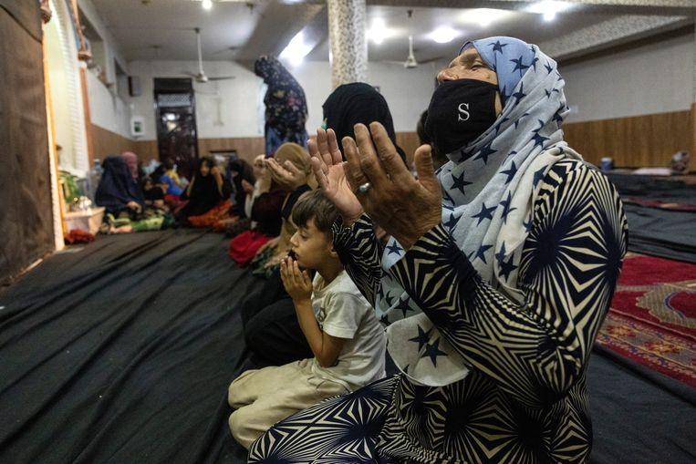 Afghaanse vluchtelingen bidden in de moskee in Kabul waar ze een heenkomen hebben gezocht. Duizenden Afghanen hebben hun steden en dorpen verlaten vanwege de opmars van de Taliban.  Beeld Getty Images