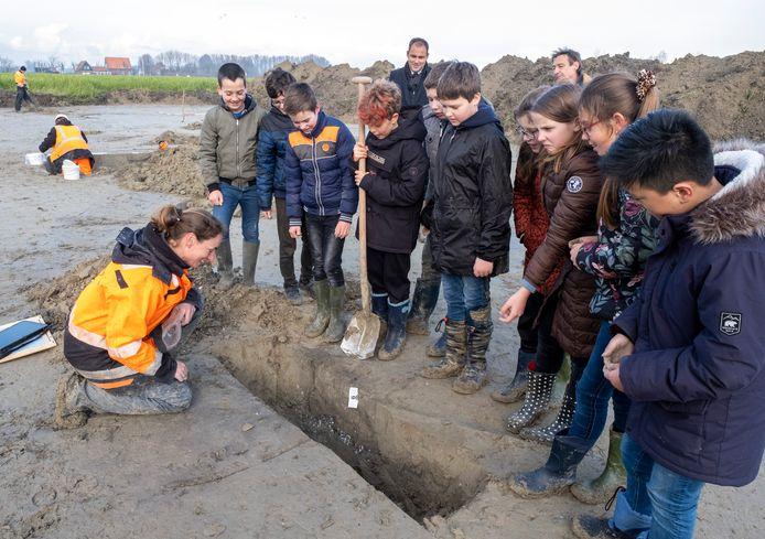 Archeologe Sentine Kodde geeft scholieren uit groep 7/8 van de Palmenhof uitleg bij opgravingen aan de rand van Sint Laurens.