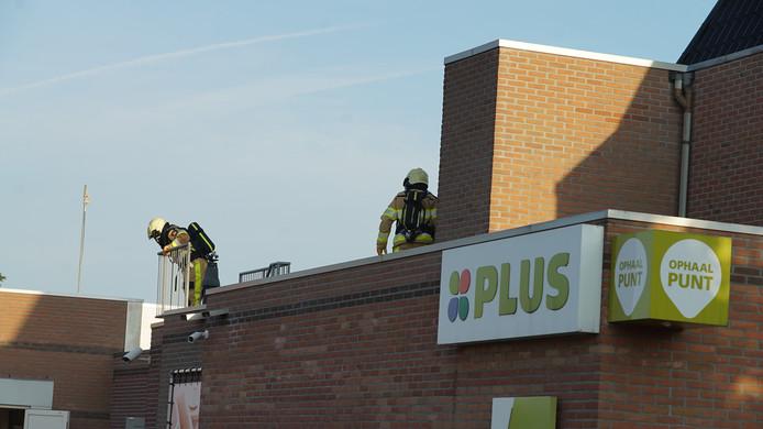 Brandweerlieden onderzoeken op het dak van Plus Supermarkt Severijn de oorzaak van de 'rookontwikkeling'.