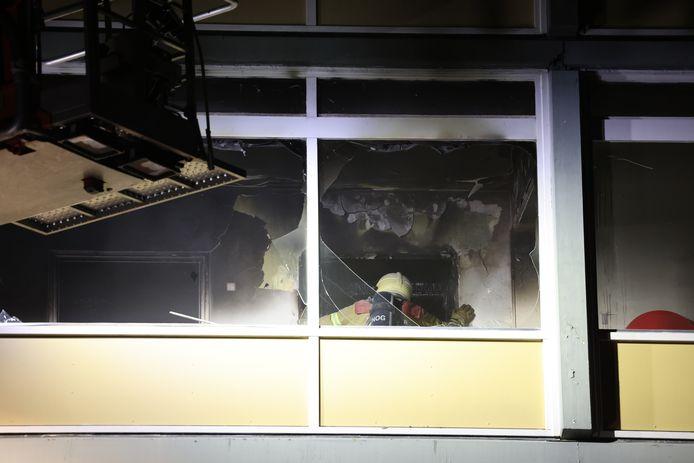 De brandweer onderzoekt de situatie op de plek waar de brand is ontstaan in de meterkast.