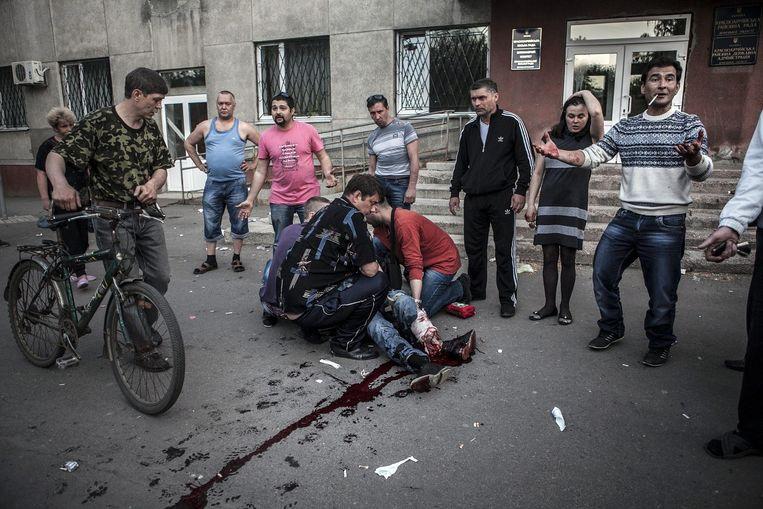 Inwoners van Krasnoarmisk helpen een gewonde man.