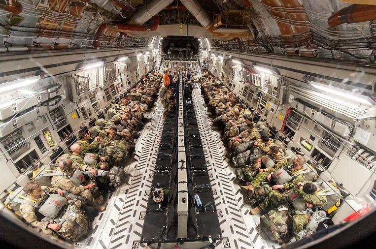 Parachutisten bereiden zich voor op een sprong aan boord van een Amerikaans C-17 Globemaster III vliegtuig. Beeld EPA