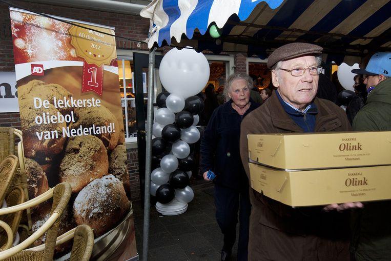Een klant met oliebollen van bakkerij Olink Beeld ANP
