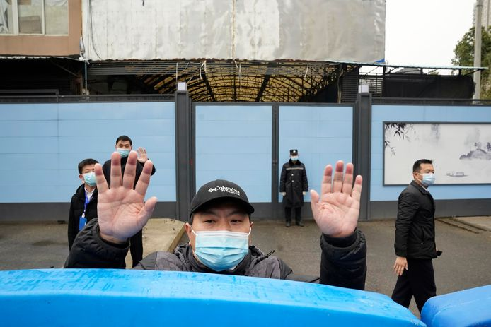 Een beveiliger schermt journalisten af van de gesloten Huanan Seafood Market  tijdens het bezoek van de WHO-onderzoeksmissie in januari.