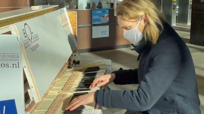 De vernielde piano in de stationshal bleek maandag nog enigszins bespeelbaar.  Op de foto David Hordijk achter de gehavende toetsen.