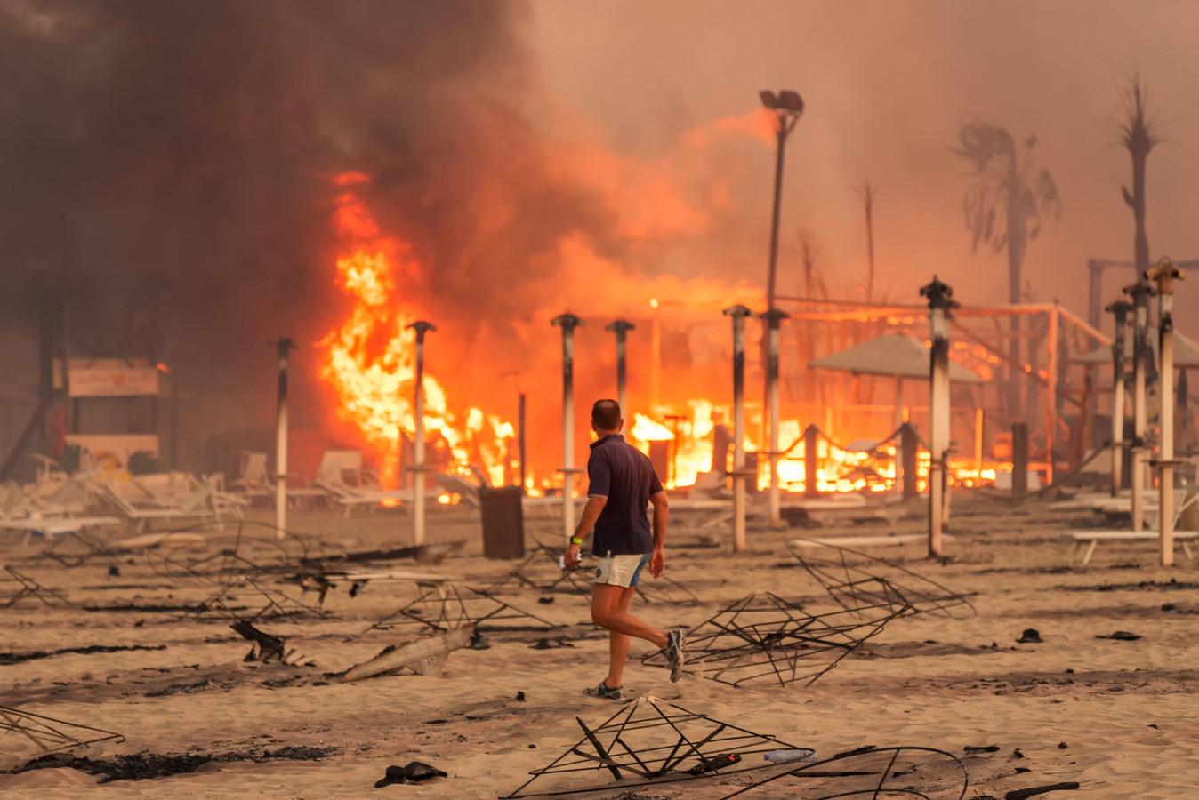 Een man loopt vlak bij een gigantische brand op een strand in Sicilië.