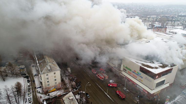 Dikke rookwolken komen uit het winkelcentrum met meerdere verdiepingen in Kemerovo, zo'n 3.600 kilometer ten oosten van Moskou.  Beeld AP