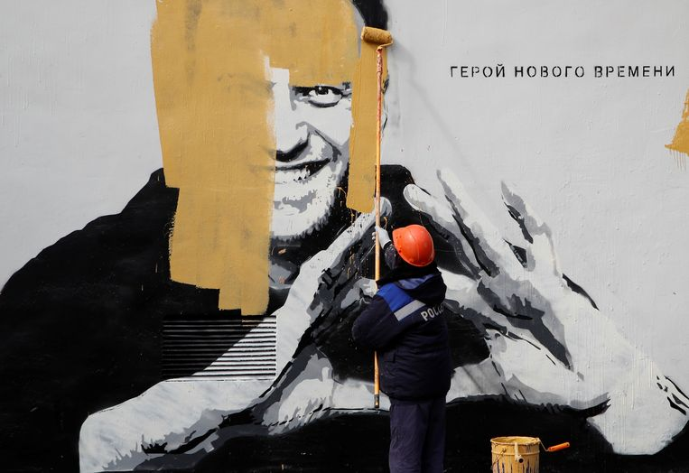 In Sint-Petersburg wordt een muur met een afbeelding van oppositieleider Alexei Navalny overgeschilderd. De tekst bij het portret: 'De held van een nieuw tijdperk'.  Beeld REUTERS