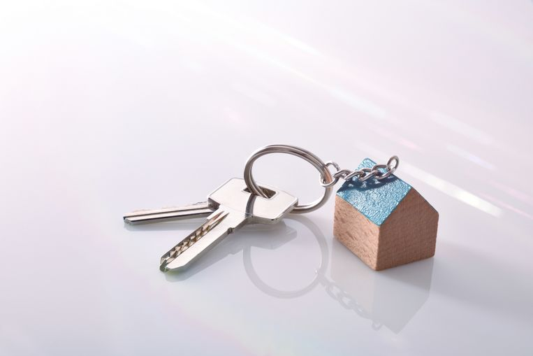 Keys with a house-shaped keyring on a white methacrylate table of a real estate agent