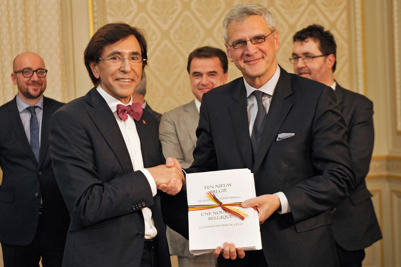 Toenmalig premier Elio Di Rupo en Vlaams minister-president Kris Peeters schudden elkaar de hand op 6 januari 2014: de zesde staatshervorming, inclusief een ruimere partijfinanciering, is een feit.