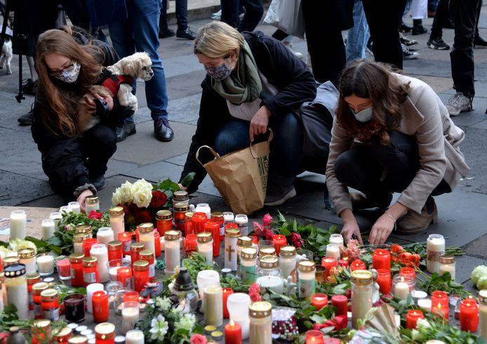 Mensen leggen bloemen neer en steken kaarsen aan aan de Porta Nigra in Trier, niet ver van de plaats waar gisteren vijf mensen om het leven kwamen nadat de Duitser Bernd W. met zijn terreinwagen door het voetgangersgebied raasde.