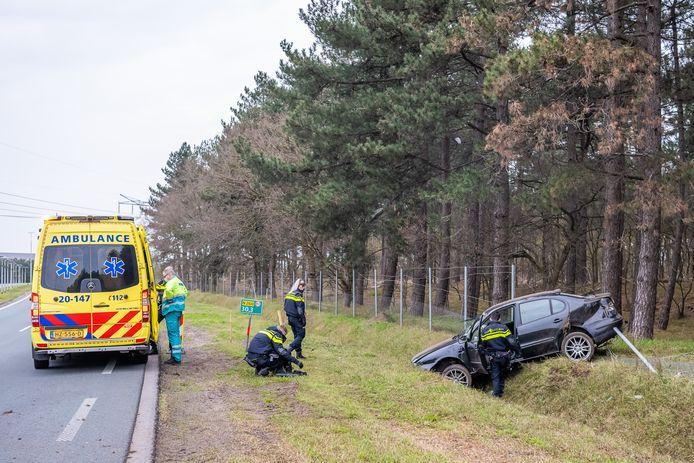 Auto belandt in greppel, bestuurder wordt medisch onderzocht door ambulancepersoneel.