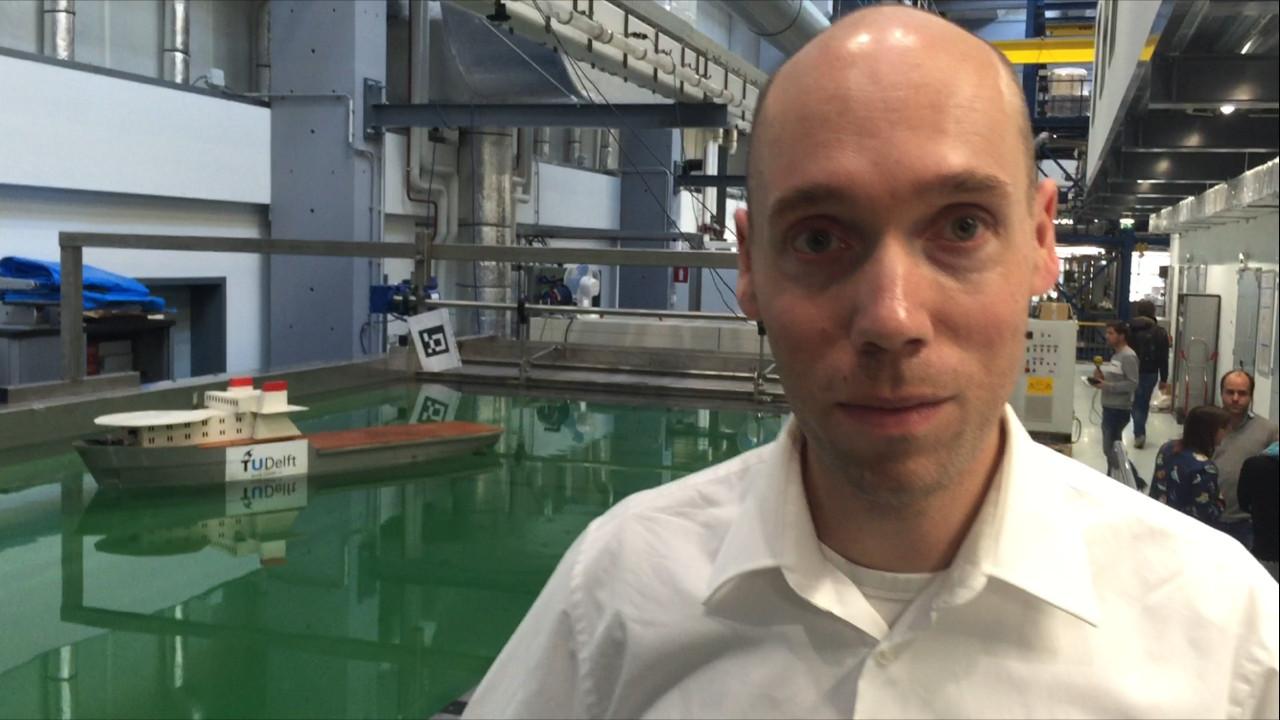 Onderzoeker Rudy Negenborn van de TU Delft. Op de achtergrond het modelrobotschip waar hij en zijn collegas onderzoek mee doen.