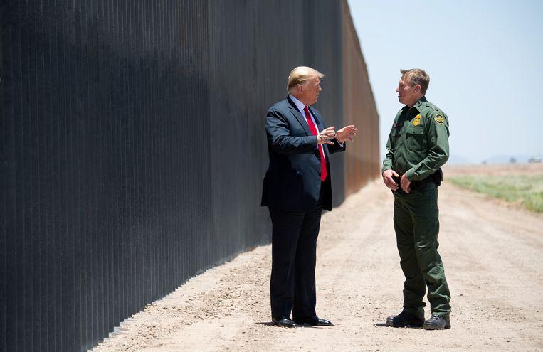 De Amerikaanse president Donald Trump bij de muur die hij laat bouwen aan de Mexicaanse grens. Beeld AFP